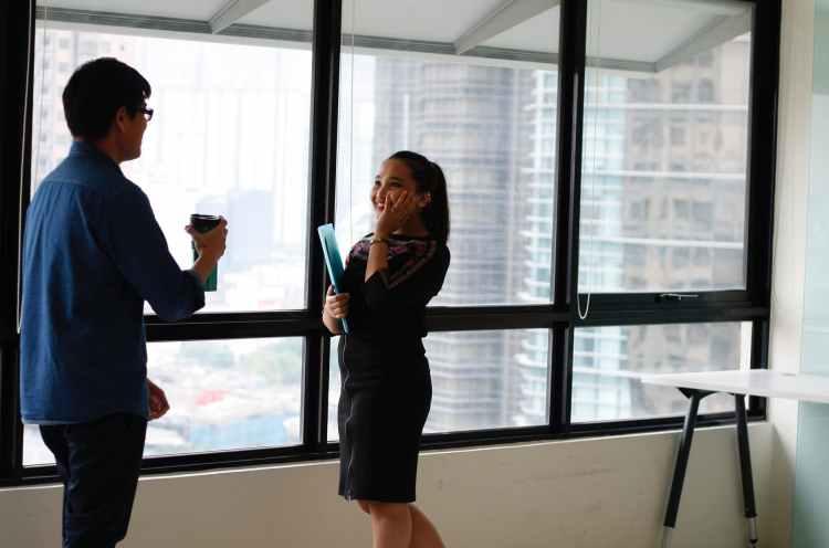 woman in black suit jacket facing man in blue denim dress shirt same standing