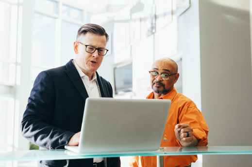 man using silver laptop beside another man